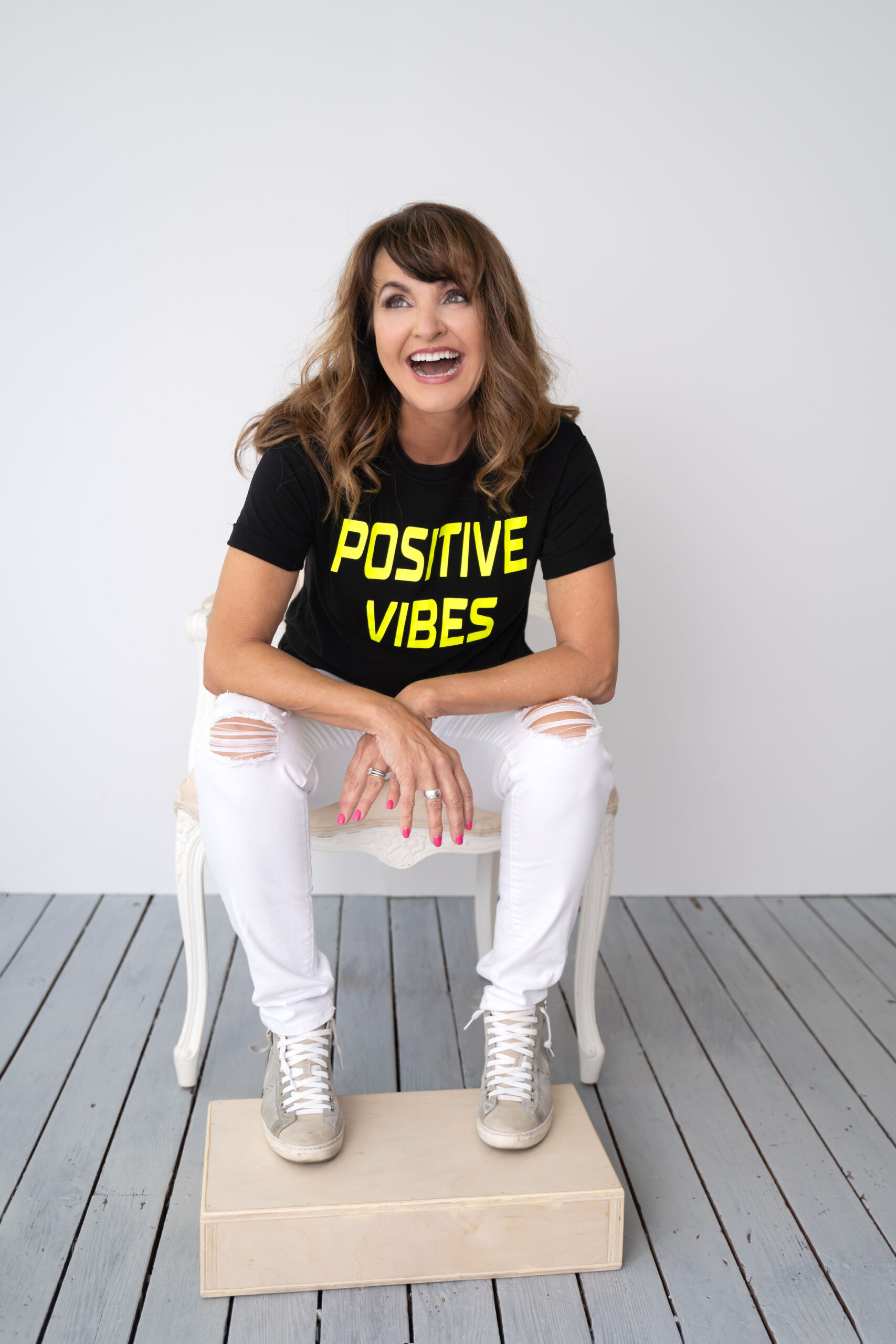 bonnie sitting in a chair wearing positive vibes shirt